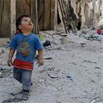 طفل في حلب ينظر إلى مبانٍ دمرها قصف نظام الأسد
