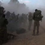 -Israeli soldiers gear up on the side of a road opposite Gaza Strip